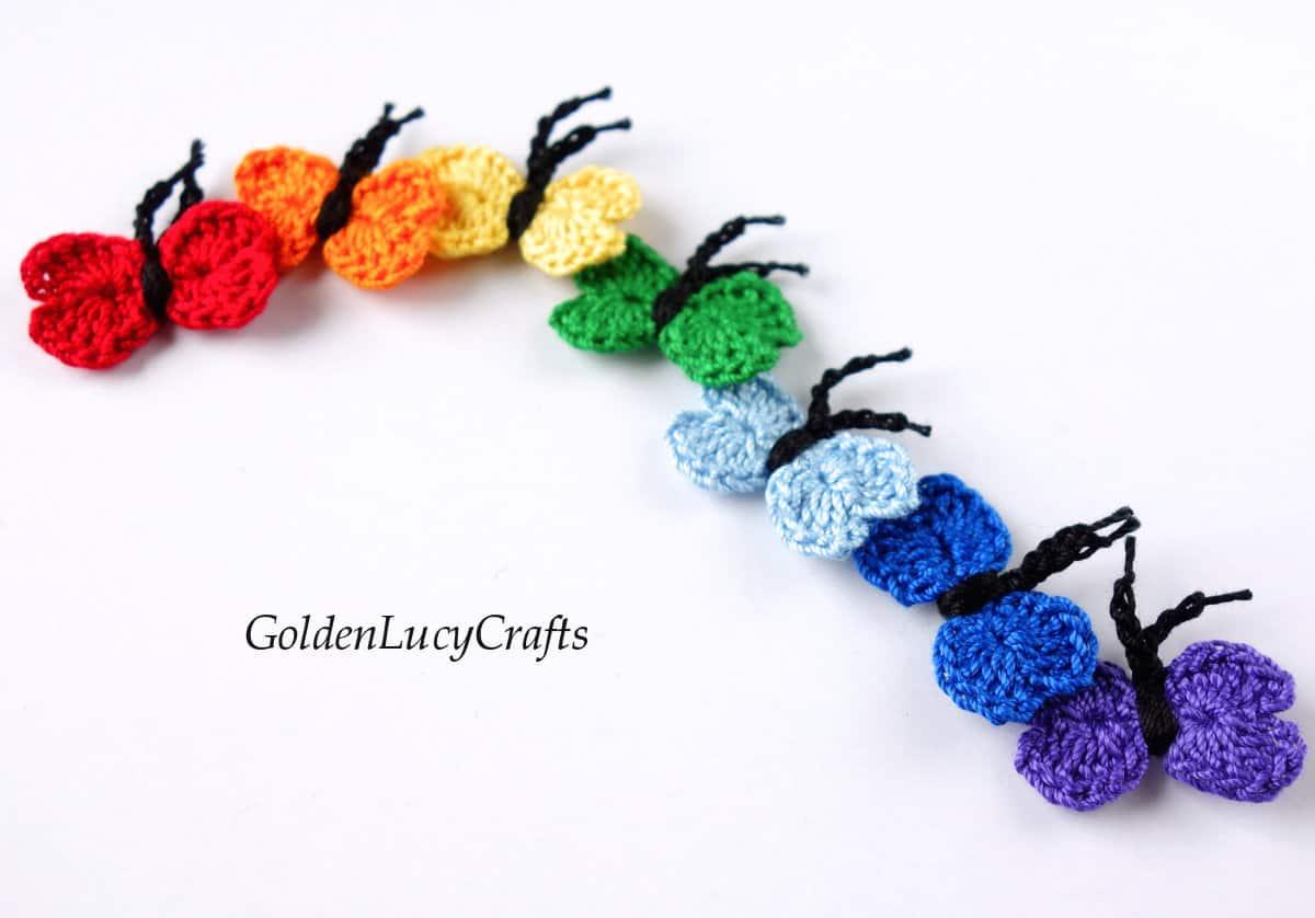 Crochet butterflies laying in a wavy line.