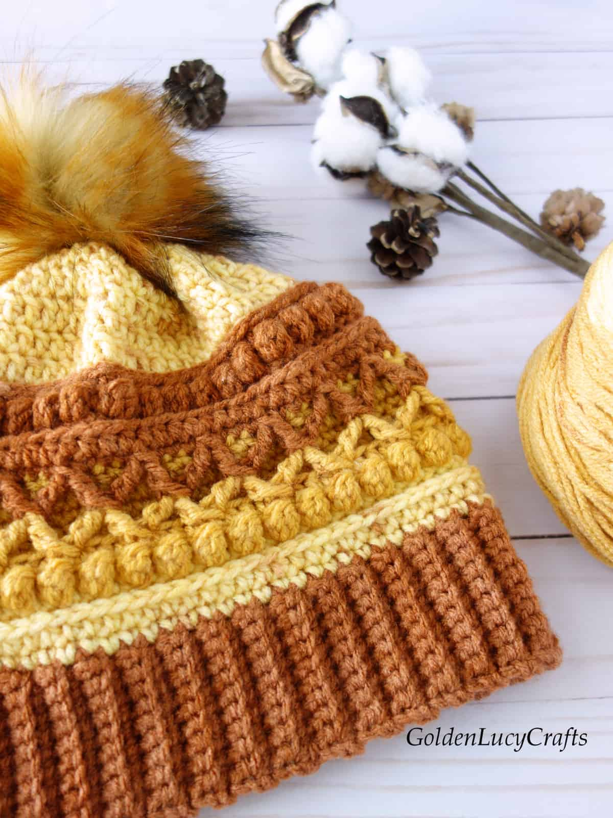 Crocheted hat in brown, orange and yellow colors embellished with fur pompom, ball of yarn, cotton branch, pine cones close up picture.
