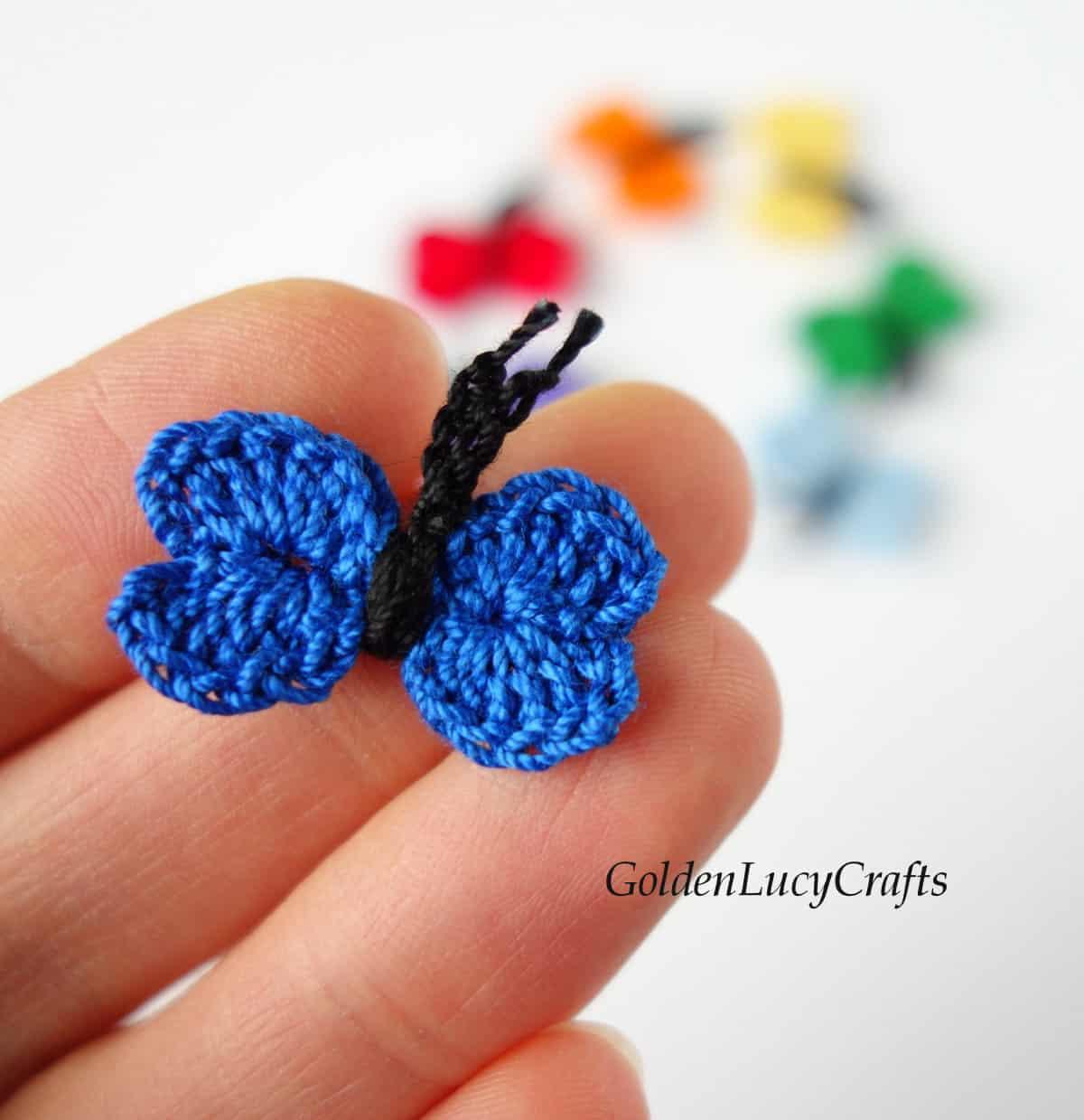 Small crochet butterfly held by fingertips.