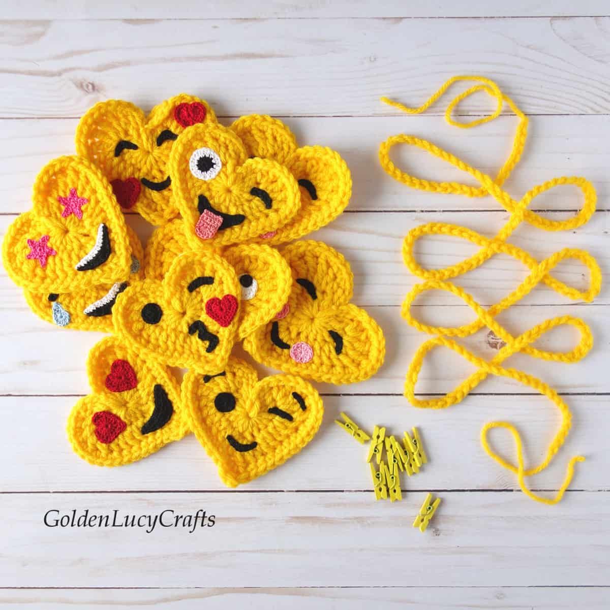 Crochet heart emojis, crocheted rope and small yellow craft clothespins.