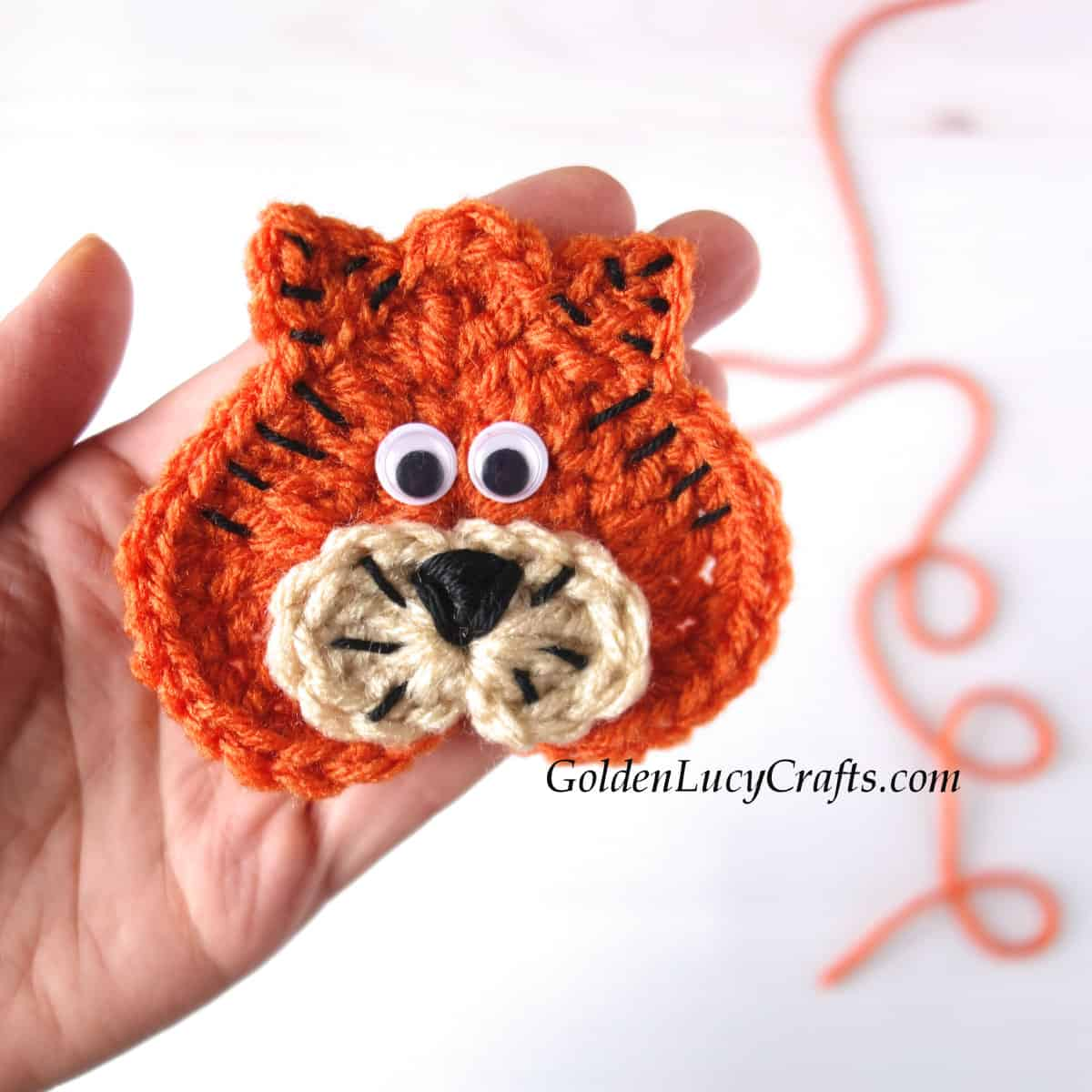 Crochet heart tiger applique in the palm of a hand.