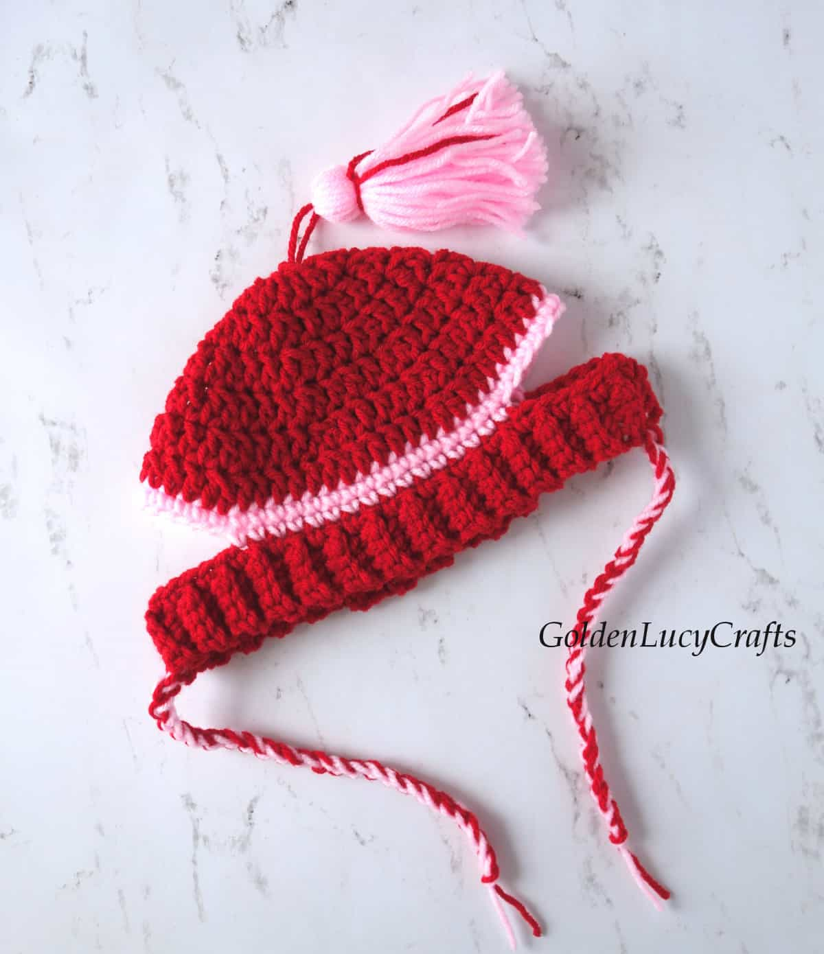 Crochet hat for a dog in red and pink colors.