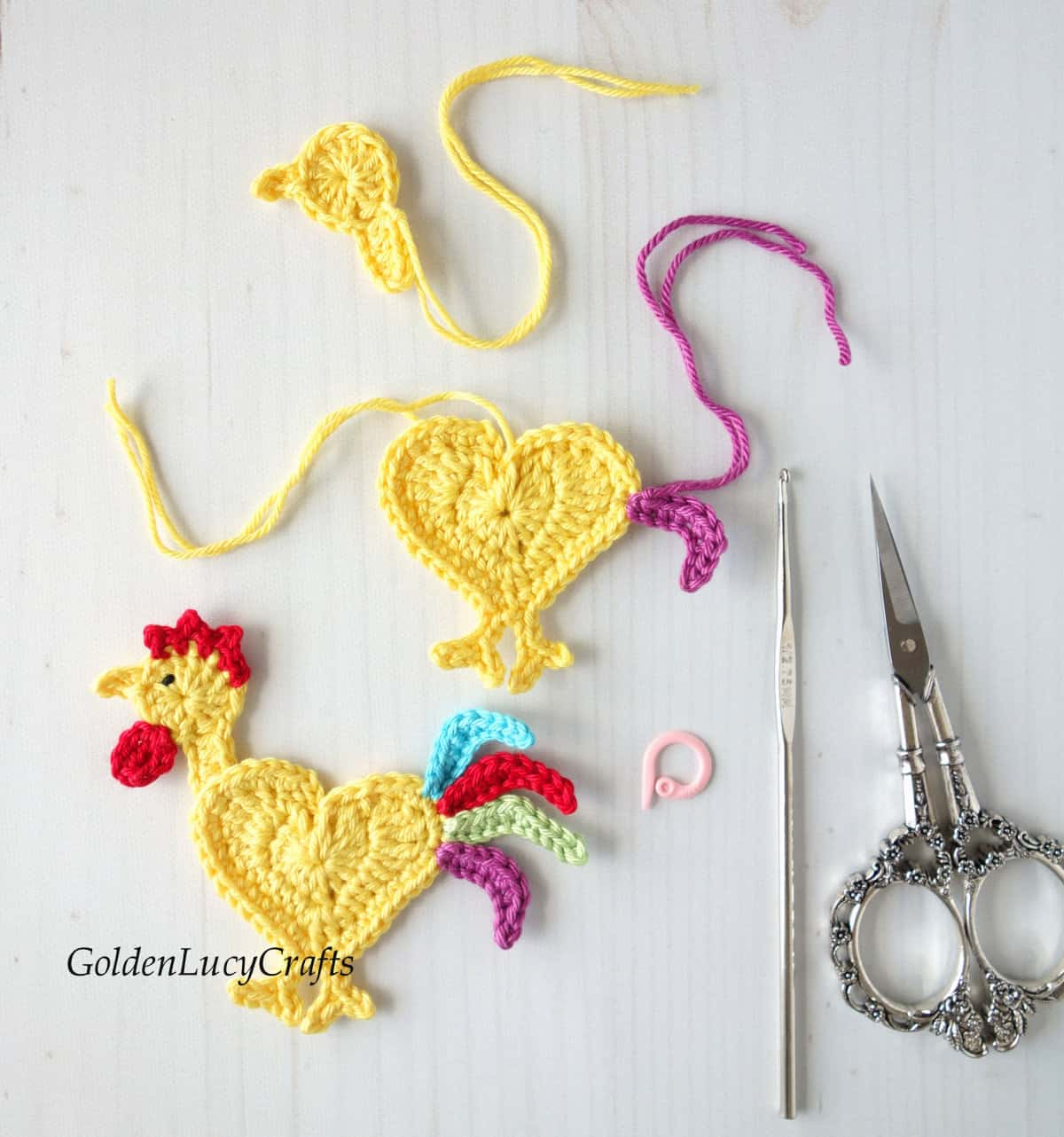 Crocheted rooster applique, parts of rooster applique, scissors, stitch marker and crochet hook.