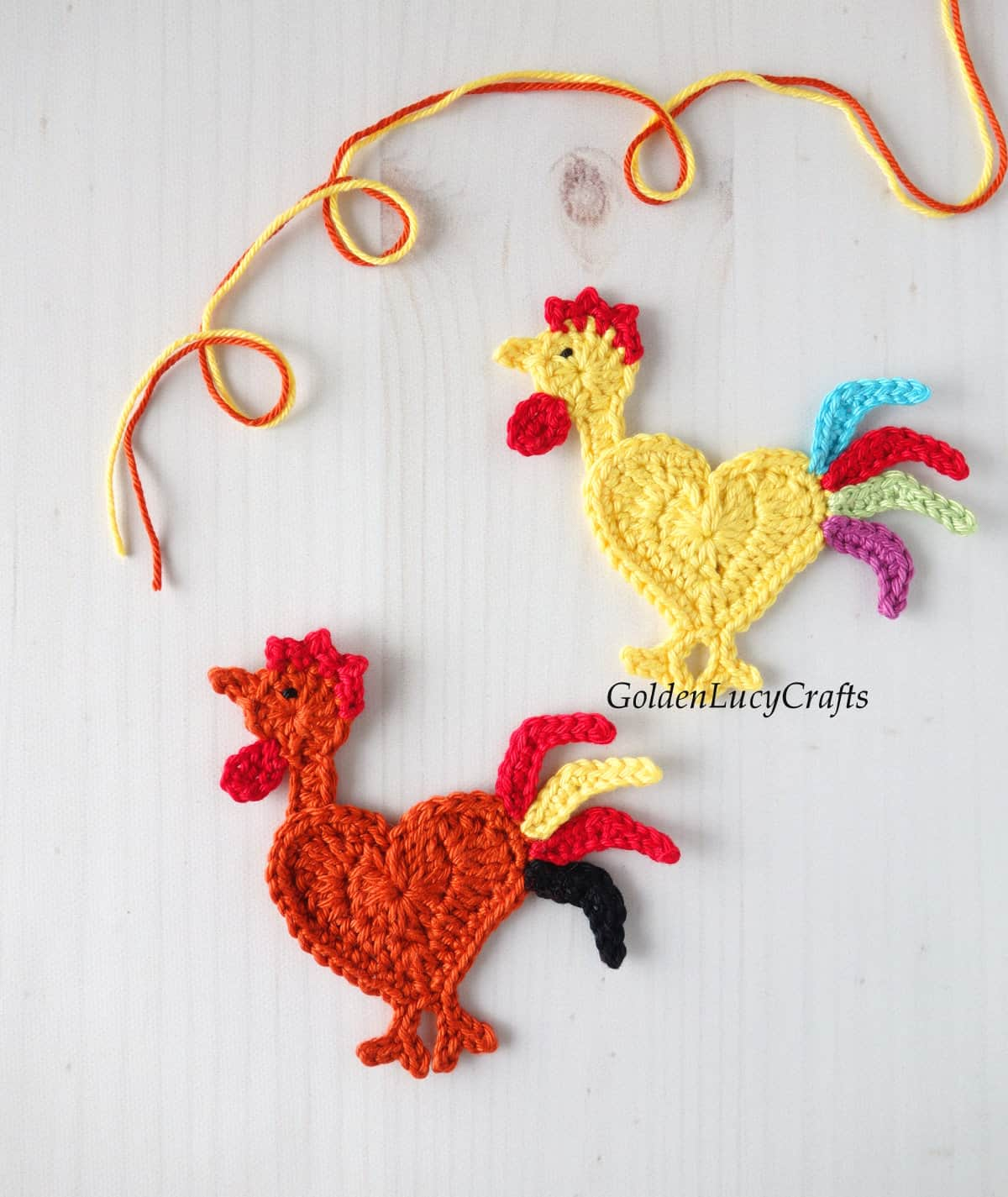 Two crocheted rooster appliques.