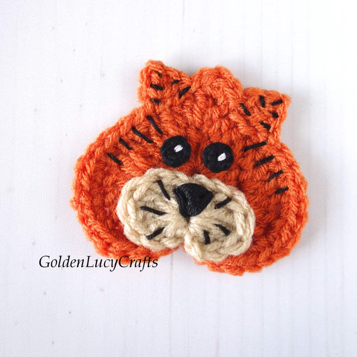 Crocheted tider applique with crocheted eyes.