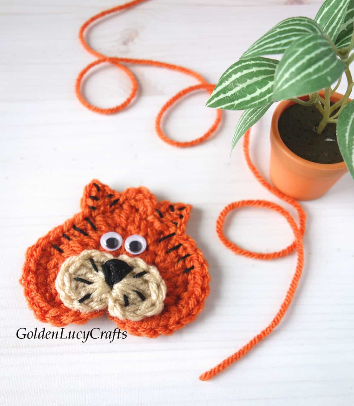 Crochet heart-shaped tiger applique, small potted plant in the background.