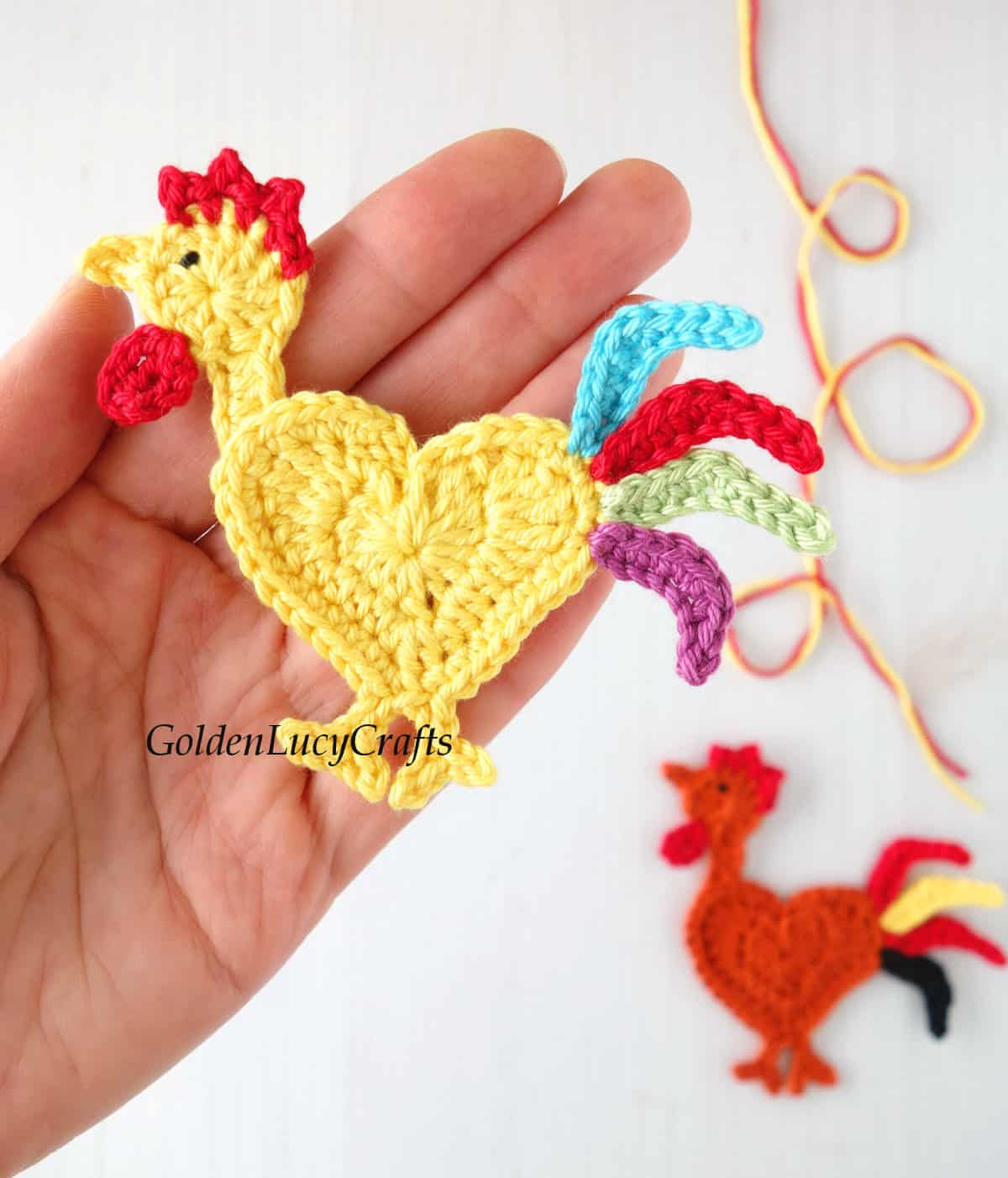 Crochet rooster applique in the palm of a hand.