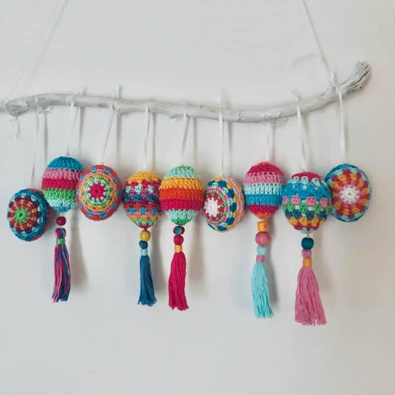 Crochet boho Easter eggs hanging on the branch.
