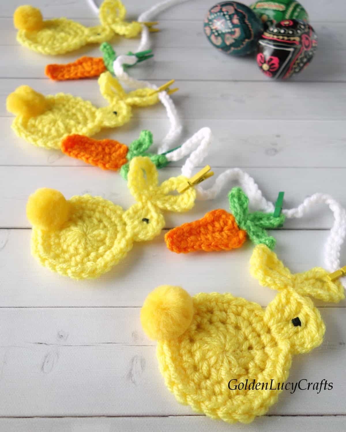 Crocheted Easter garland with bunnies and carrots close up picture, painted Easter eggs in the background.