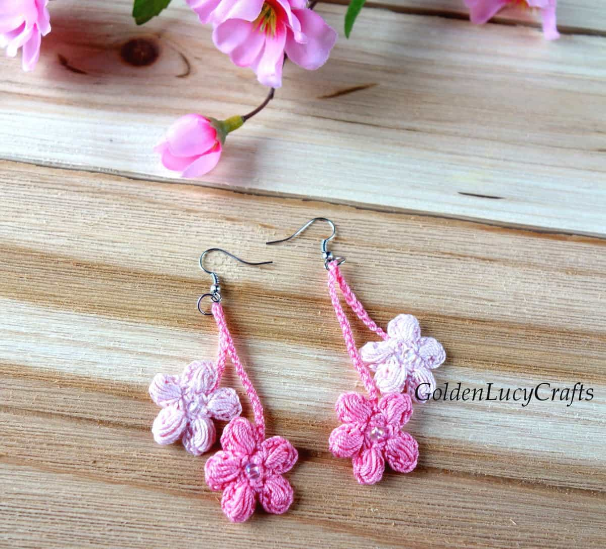 Crocheted cherry blossom earrings on wooden surface.