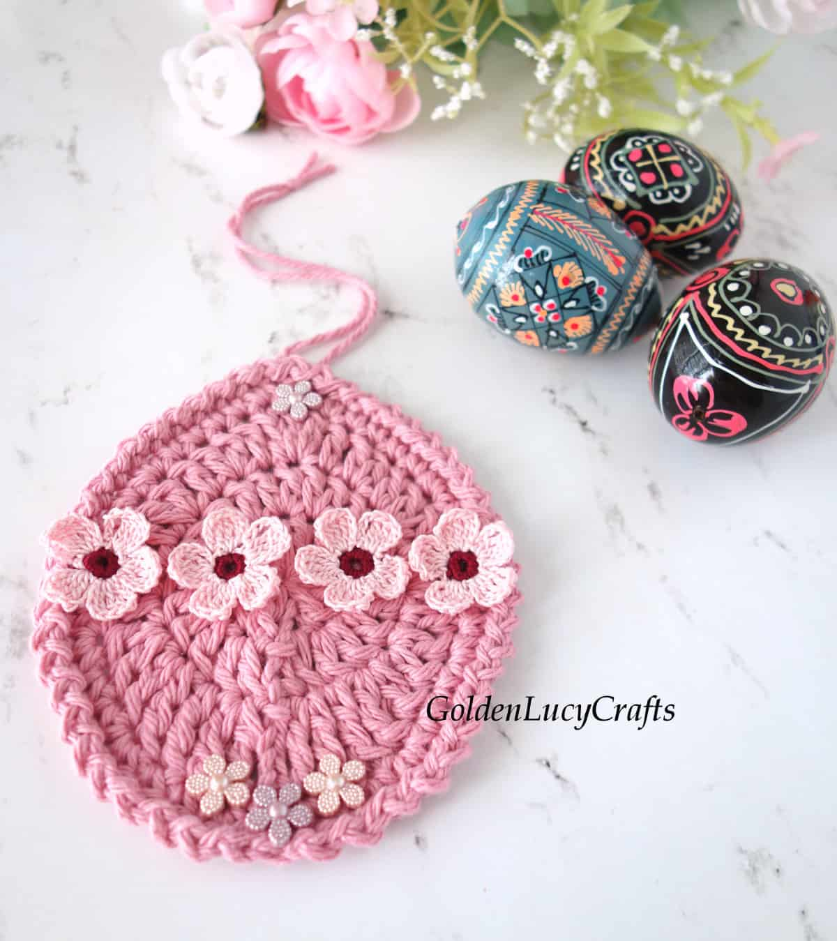 Crocheted Easter egg ornament embellished with small flowers, three wooden painted eggs next to it.