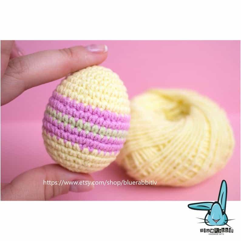 Crocheted Easter egg held by fingertips.