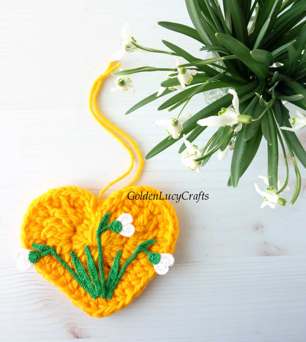 View from the top - crocheted yellow heart embellished with crocheted snowdrops and real snowdrops in a vase.