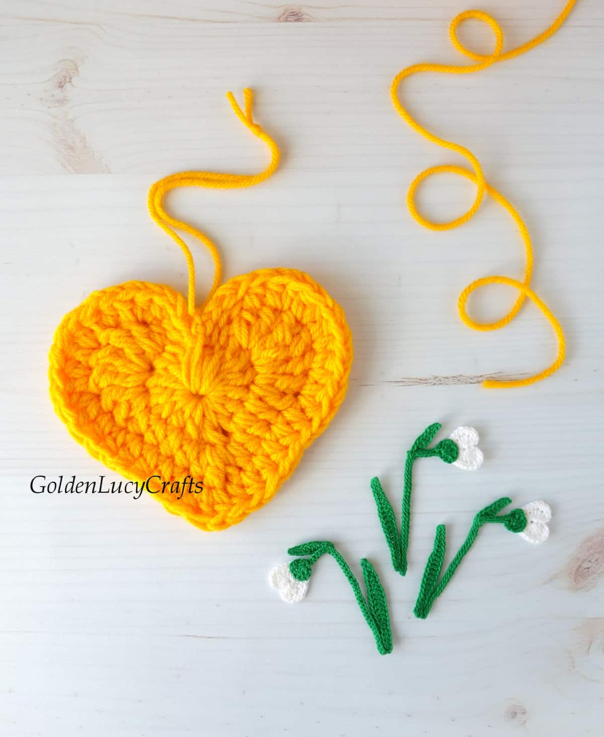 Crocheted yellow heart and crocheted snowdrop applique.