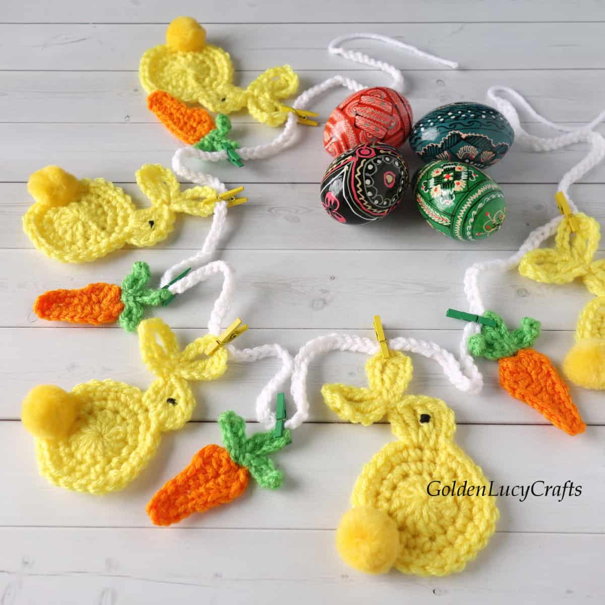Crocheted Easter garland with bunnies and carrots laying on surface with painted Easter eggs next to it.