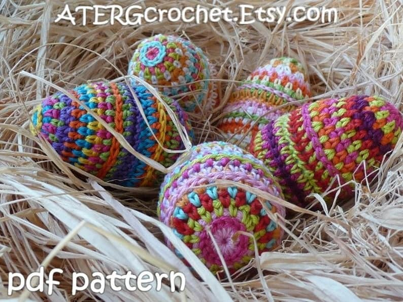 Crocheted eggs laying in hay.