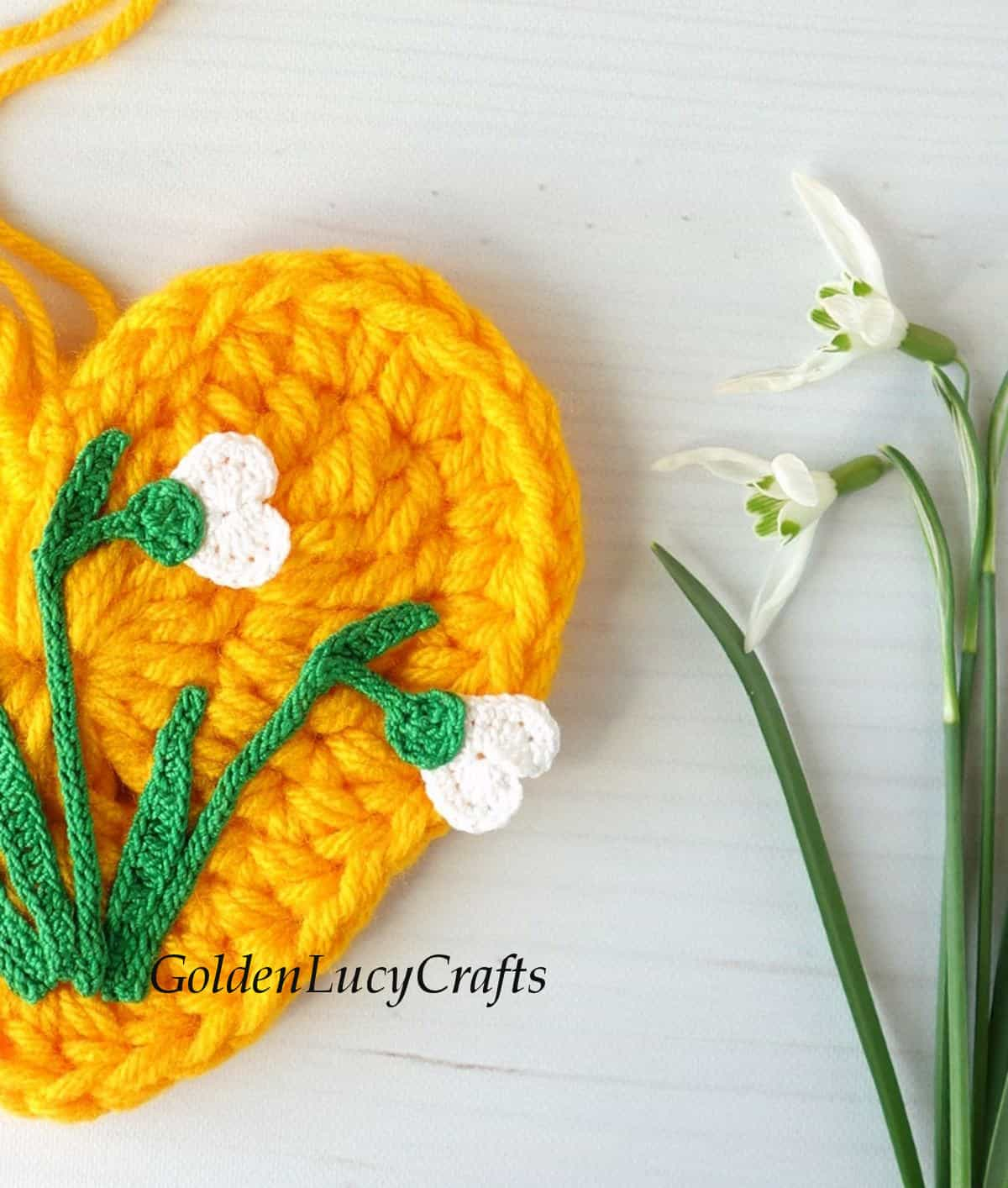Close up image - half of crocheted yellow heart embellished with snowdrop applique and real snowdrops.