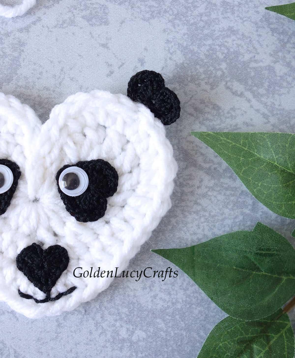 Half of crocheted panda face close up image.