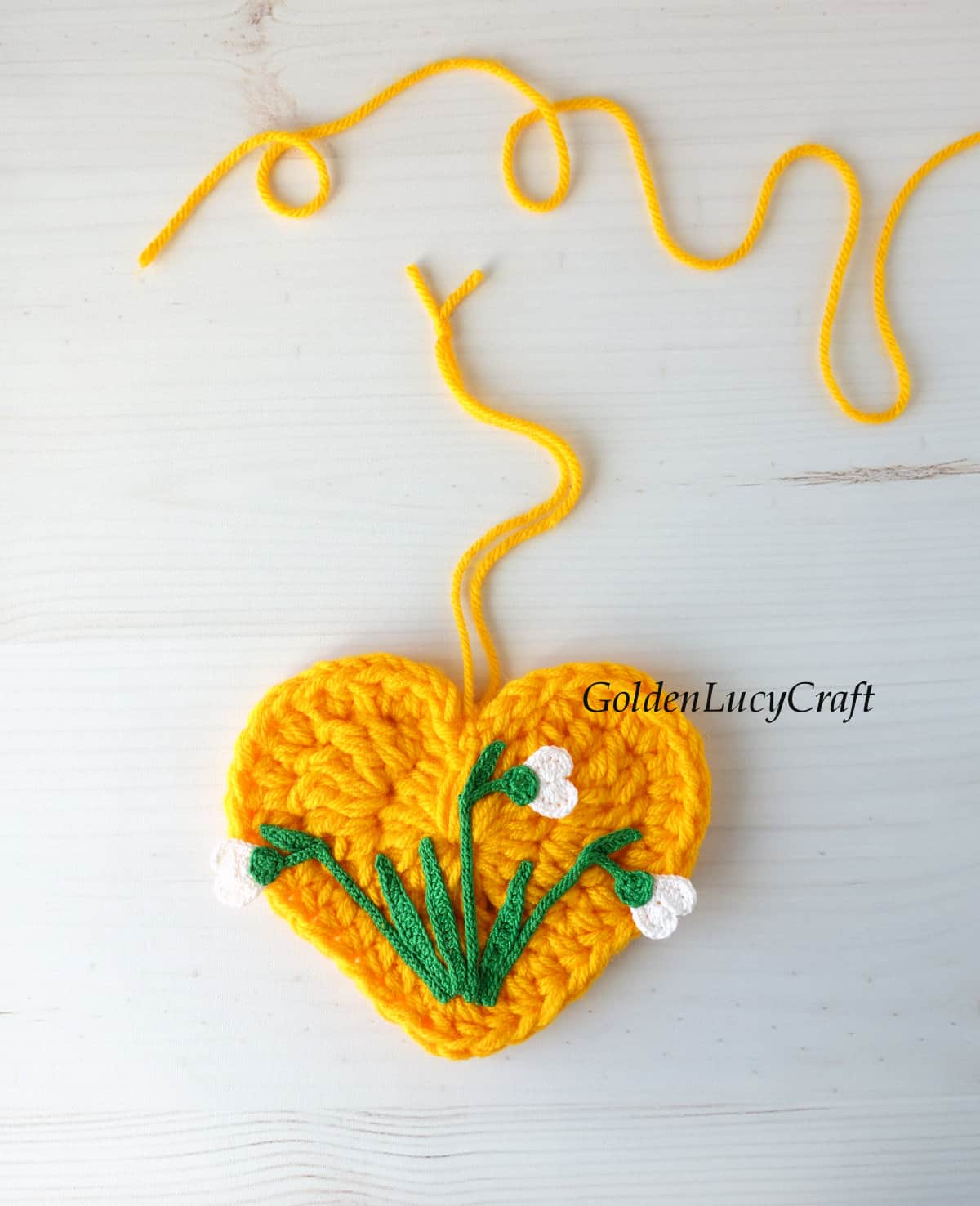 Crocheted yellow heart with crocheted snowdrops on it.