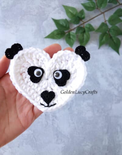 Crochet panda applique in the palm of a hand.