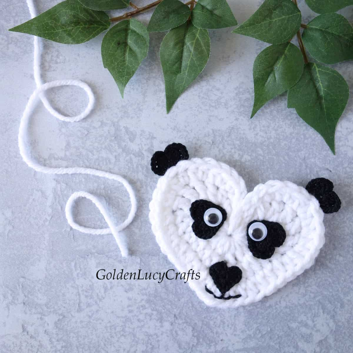 Crochet heart-shaped panda applique.