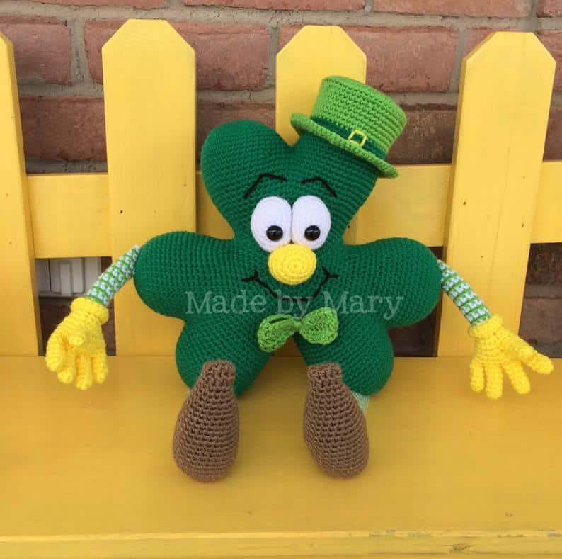 Crocheted shamrock toy sitting on a yellow bench.