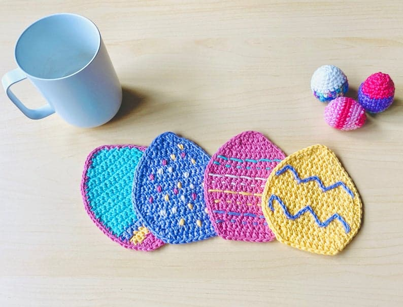 Crochet Easter egg coasters, mug and three crocheted eggs.