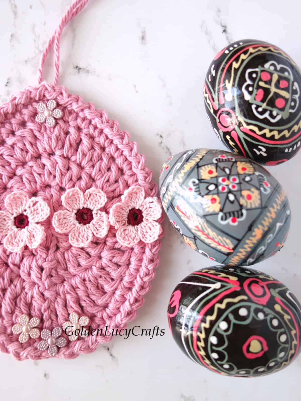 Close up image of crocheted Easter egg ornament embellished with small flowers, three wooden painted eggs next to it.