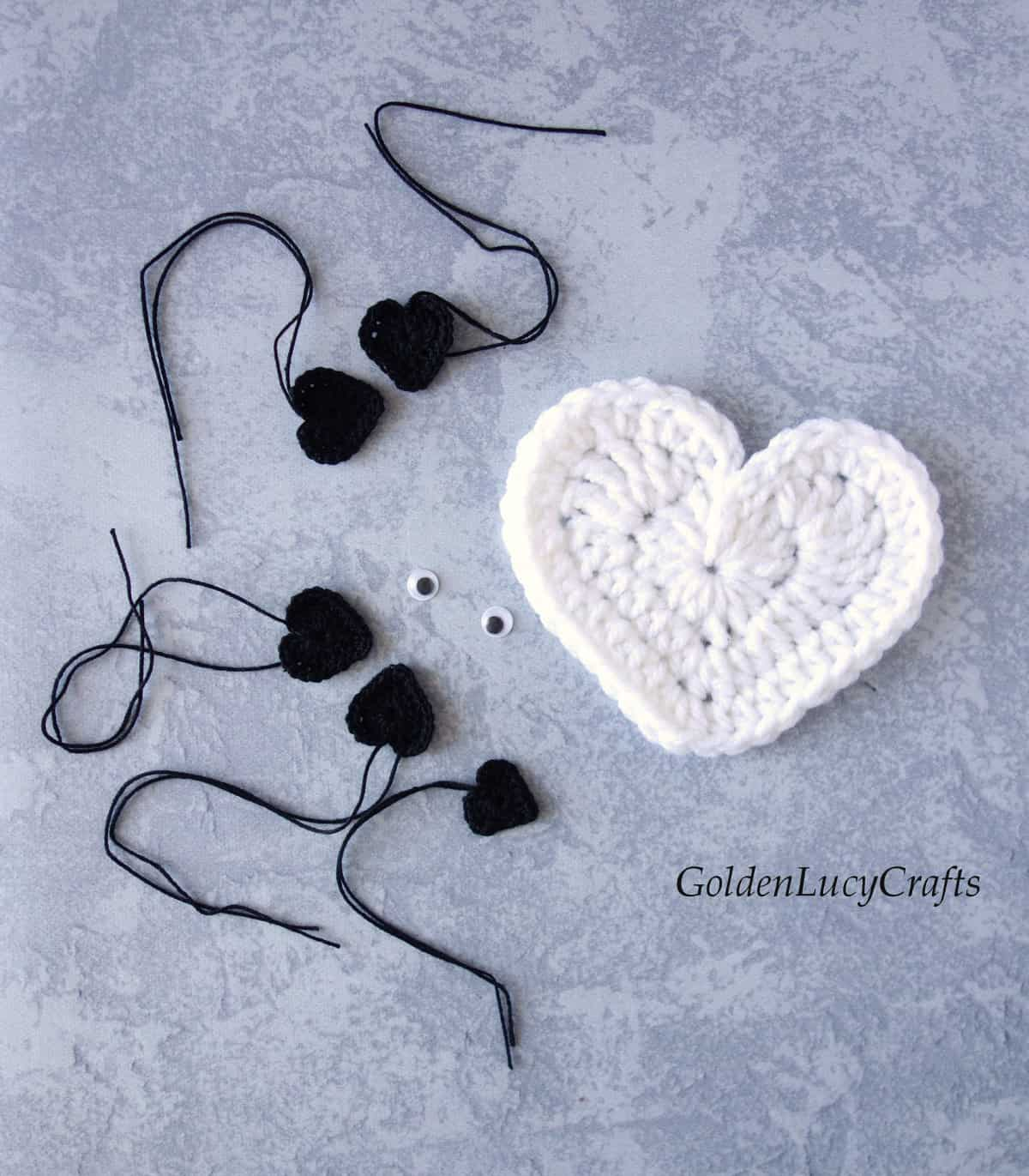 Large white crocheted heart, five small black hearts, two craft googly eyes.