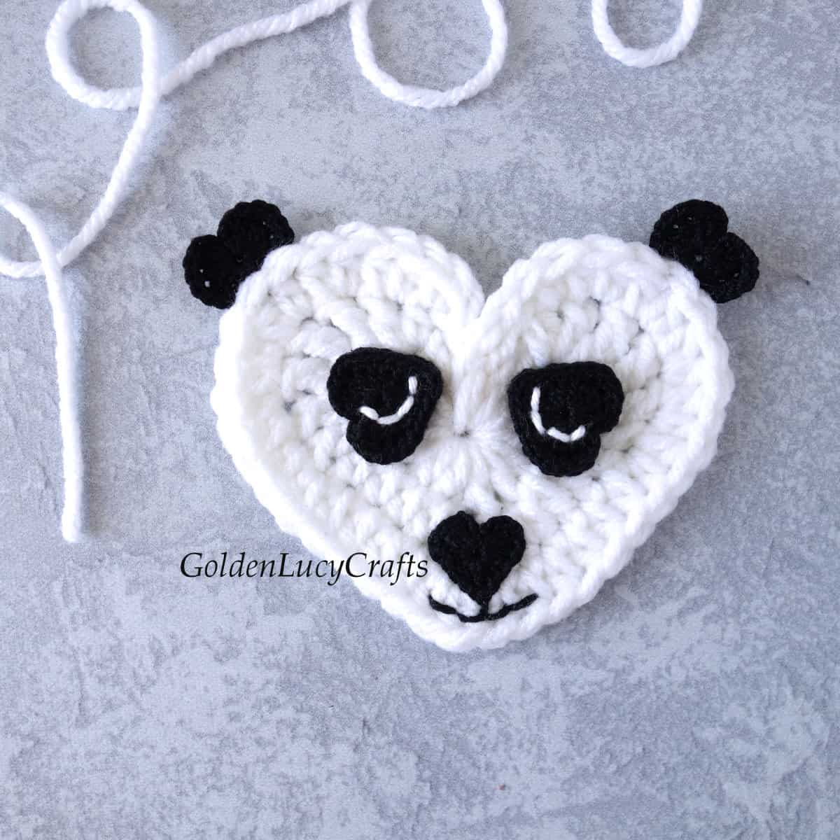 Crochet panda applique with embroidered eyes.