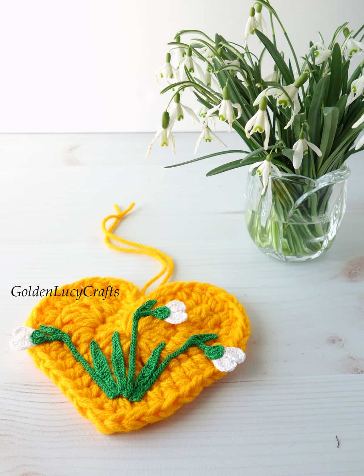 Crocheted yellow heart with crocheted snowdrops on it laying on the surface, real snowdrops in a vase in the background.
