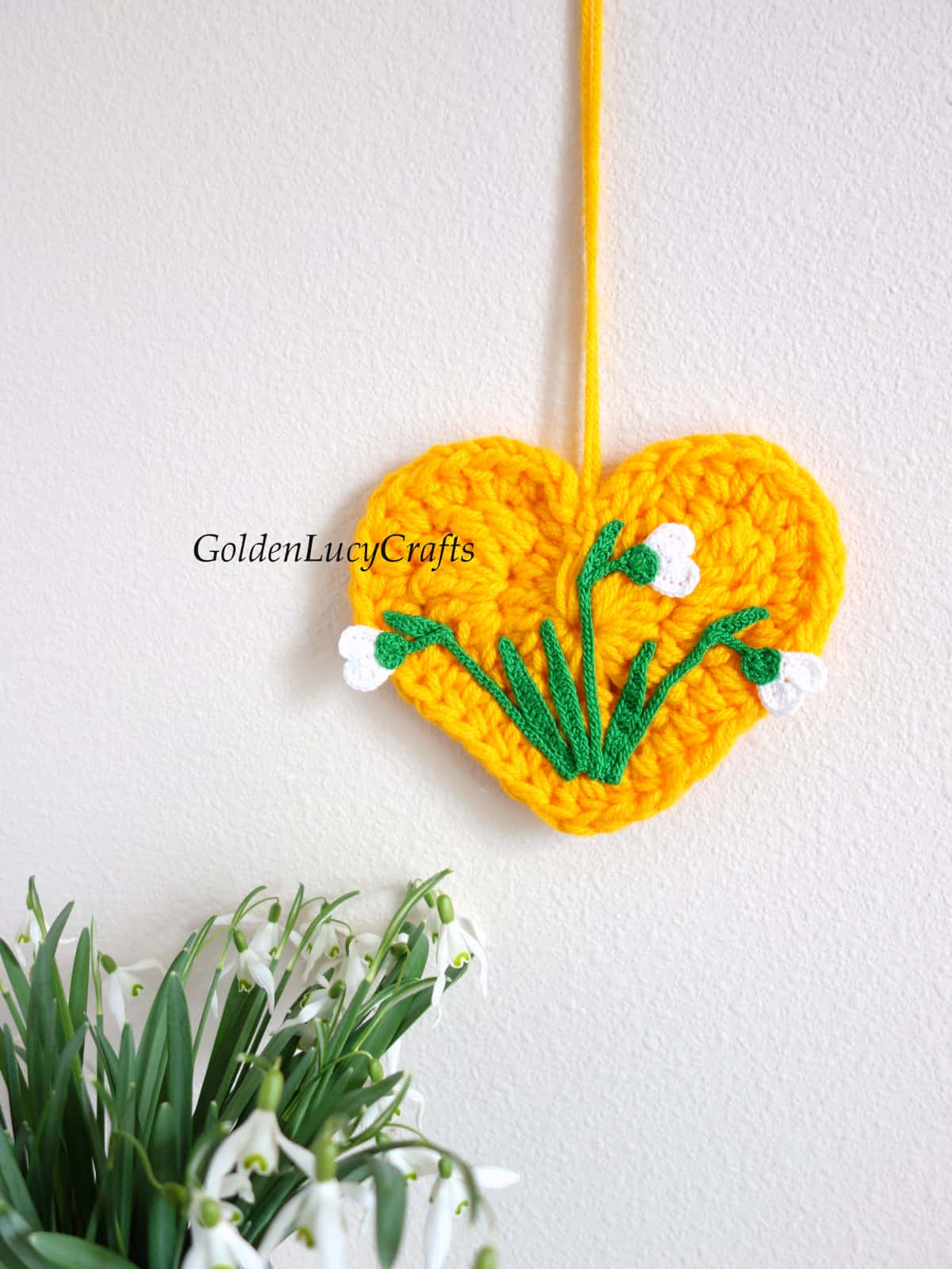 Crocheted yellow heart with crocheted snowdrops on it wall decor, real snowdrops in a vase.