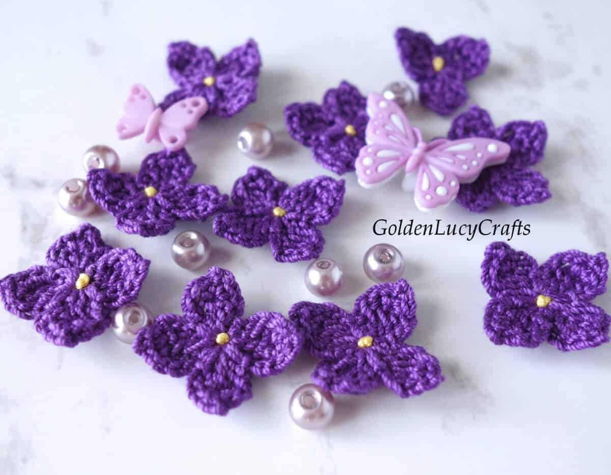 Crocheted lilac flowers, beads and butterfly buttons.