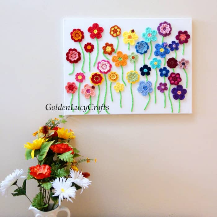 Crochet flowers on canvas wall art.