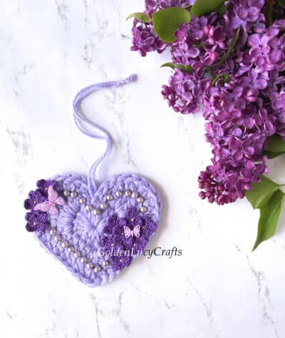 Crocheted heart embellished with crochet lilac flowers and beads, real lilac flowers laying on surface.