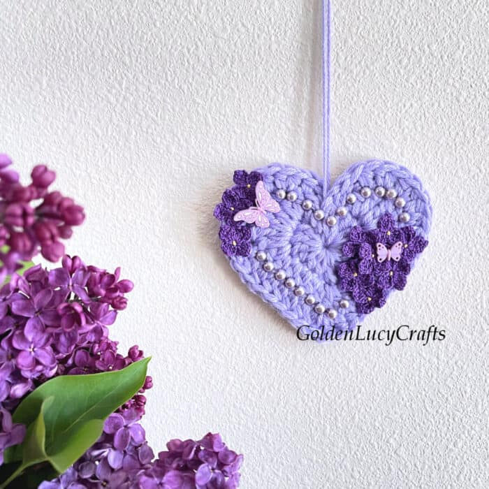 Crocheted heart embellished with crochet lilac flowers and beads hanging on the wall.