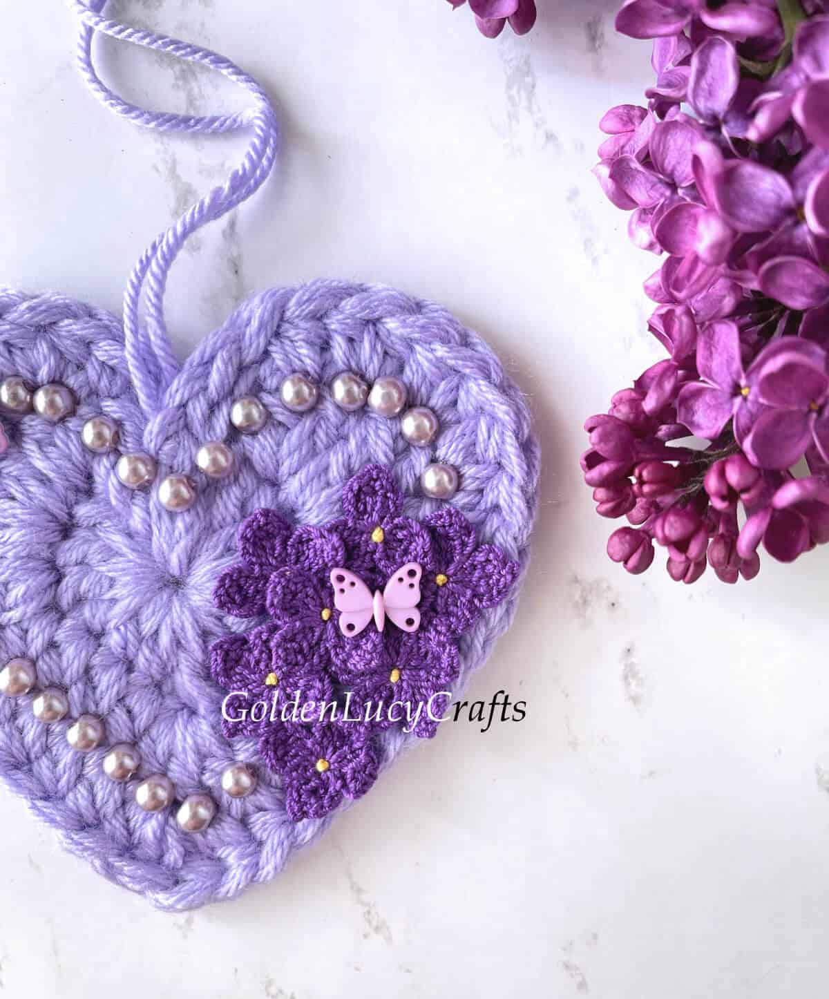 Crocheted heart embellished with crochet lilac flowers and beads close up picture.