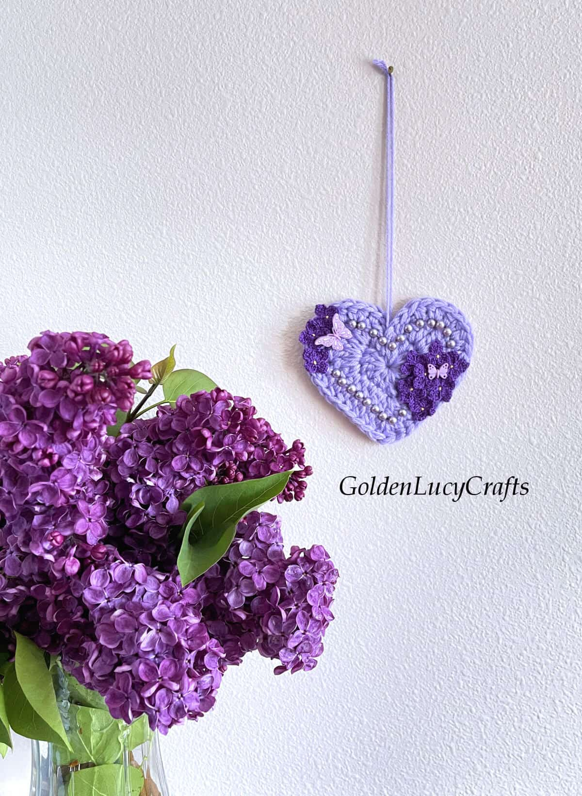Crocheted heart embellished with crochet lilac flowers and beads hanging on the wall, lilac bouquet in a base next to it.
