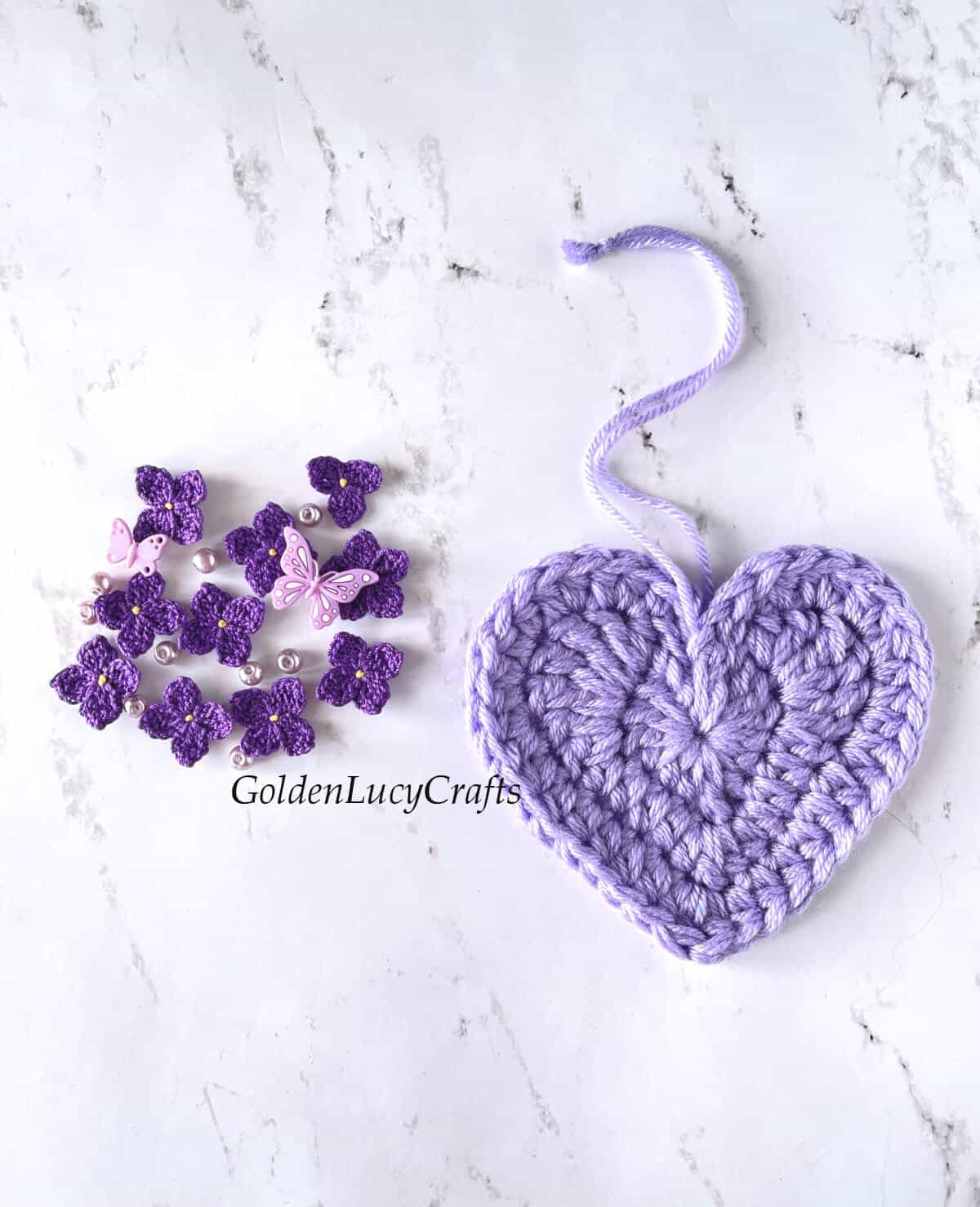 Crocheted heart ornament, crocheted lilac flowers, beads and butterfly buttons laying on a surface.