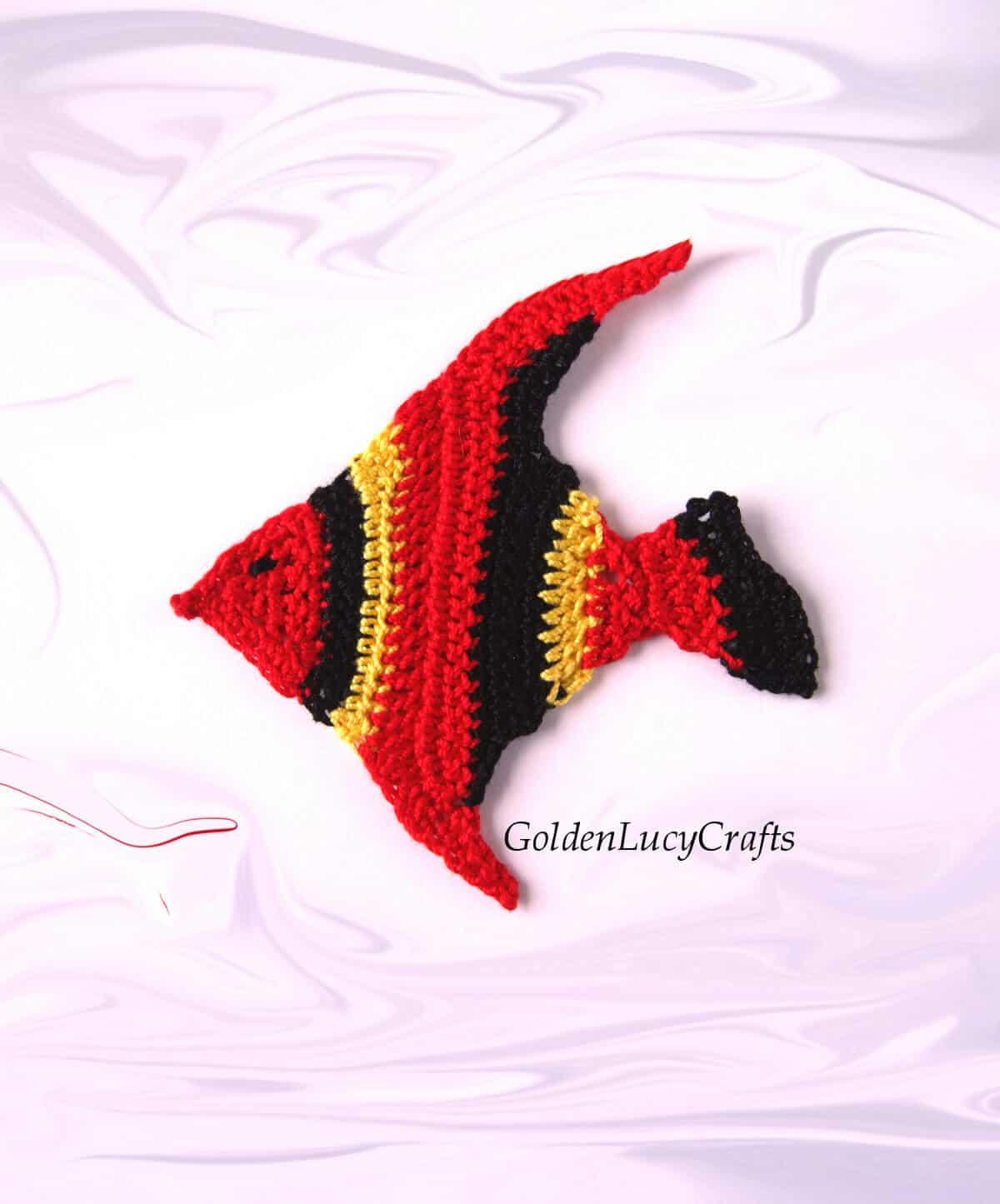 Aplique de crochet de pez en colores rojo, negro y amarillo.