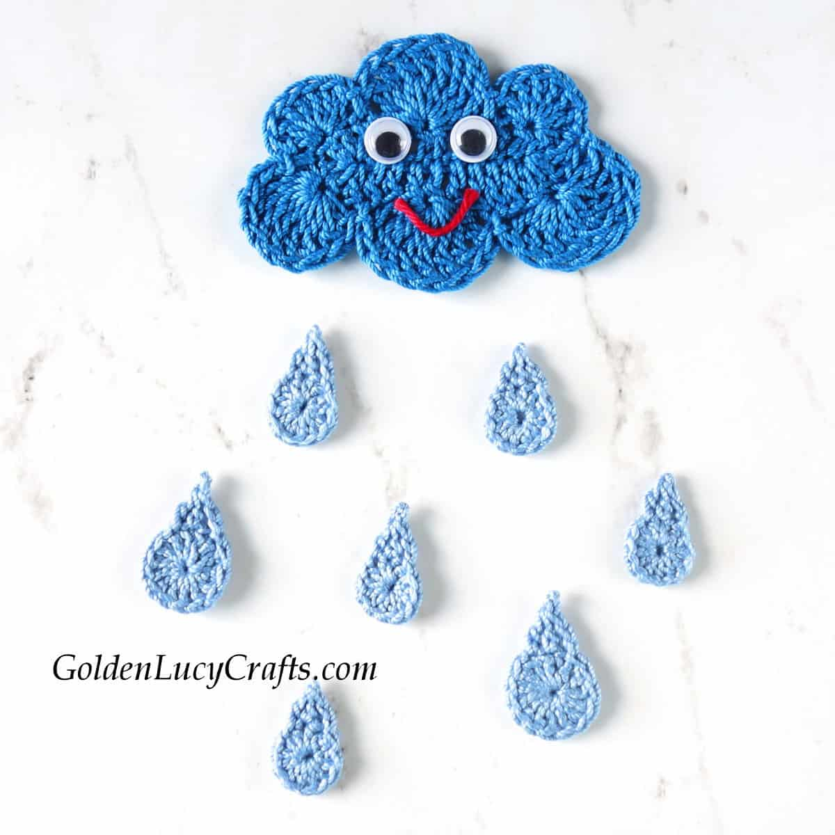 Crocheted cloud with googly eyes and smile, raindrops applique.