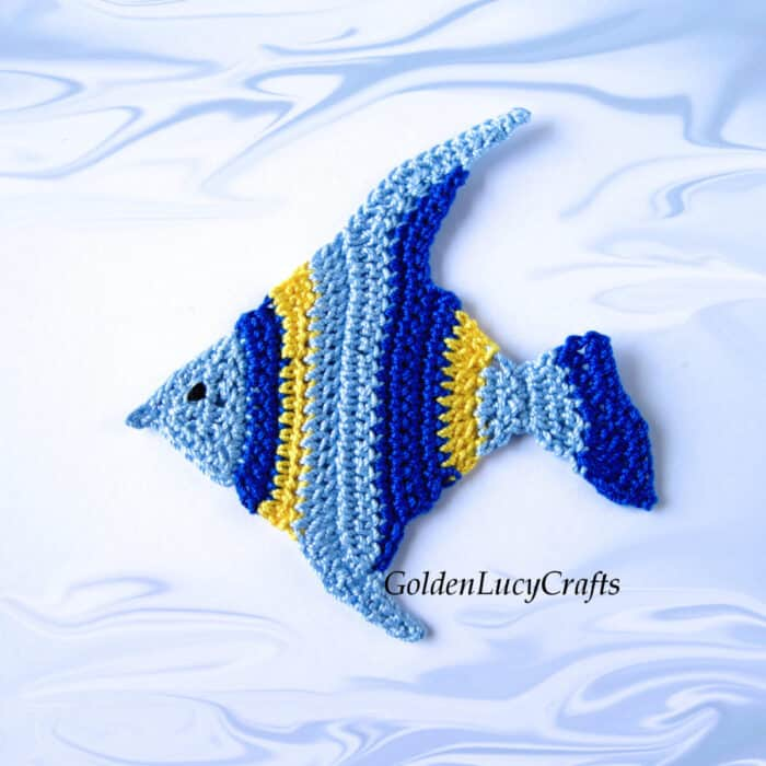 Crocheted tropical fish applique in shades of blue and yellow colors.