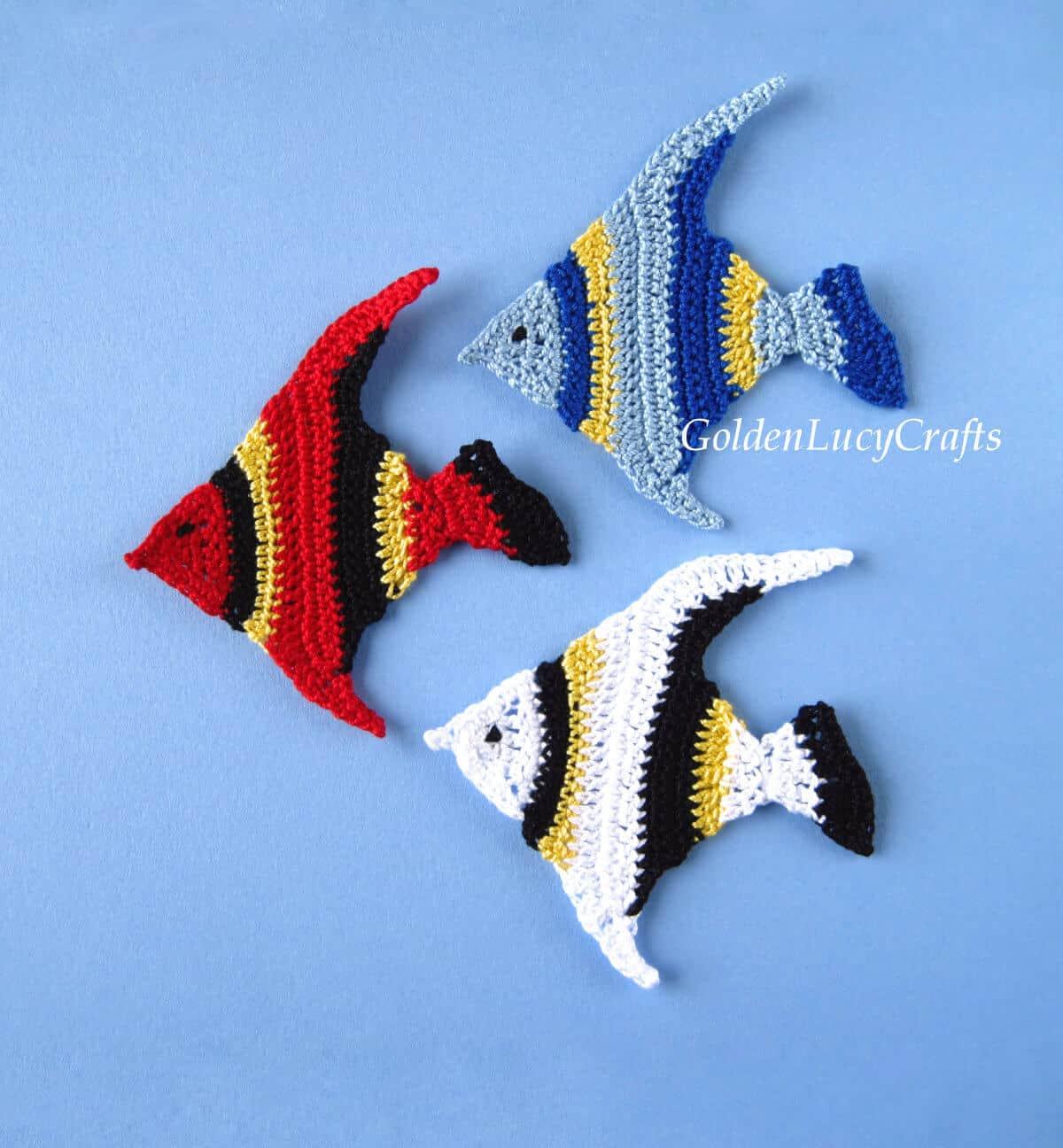 Tres apliques de peces de colores de ganchillo sobre el fondo azul.