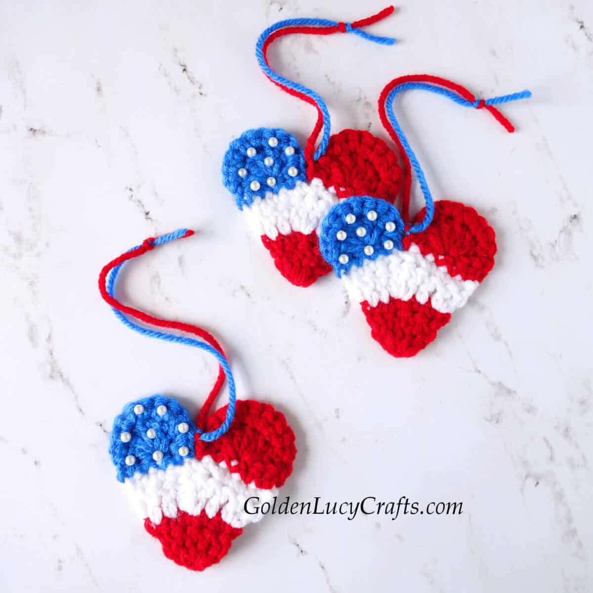 Three crocheted hearts in patriotic colors - red, white and blue.
