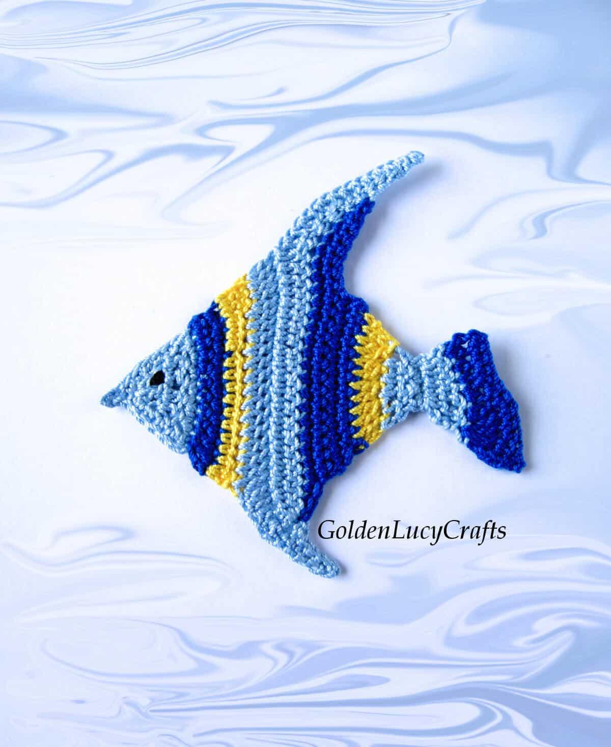 Aplique de ganchillo de peces tropicales en tonos azules y amarillos.