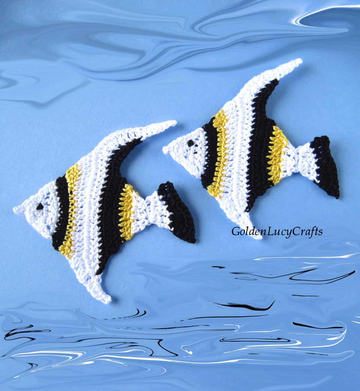Dos apliques de crochet de peces en colores blanco, negro y amarillo.