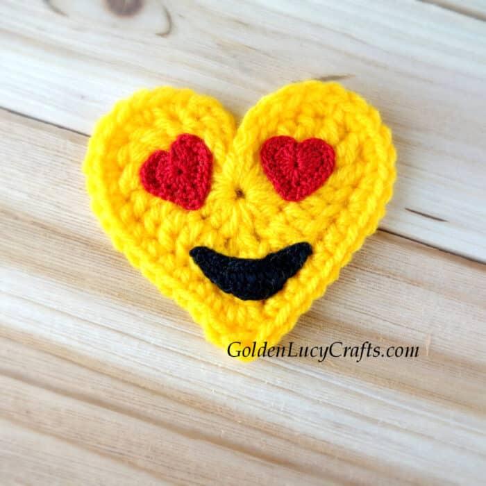 Crochet heart-shaped emoji applique heart eyes emoji.