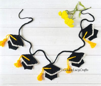 Crocheted graduation garland laying on the surface, yellow flowers in the background.