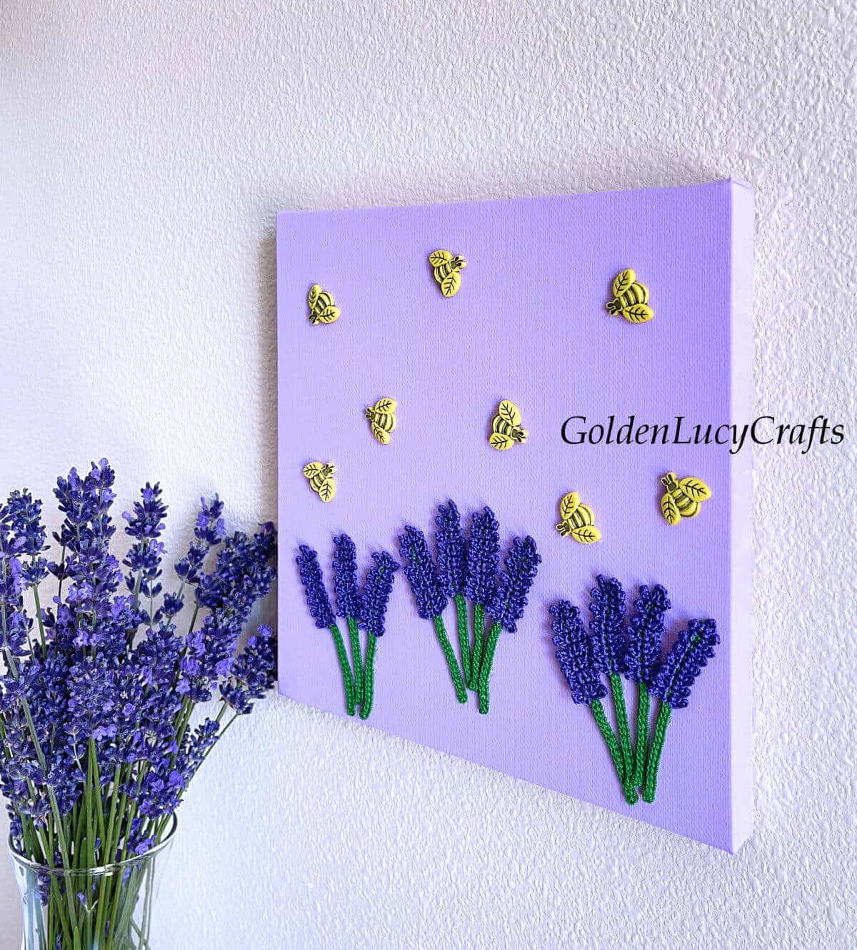 Wall art lavender and bees hanging on the wall, lavender in the vase next to it.