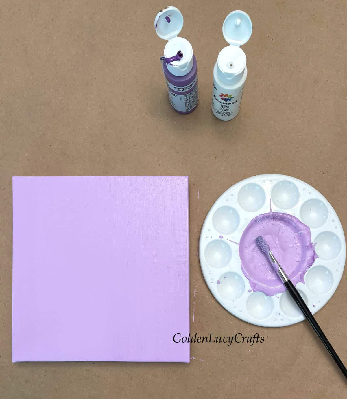 Canvas painted in light lavender color, paint brash, two open bottles of paint on the table.